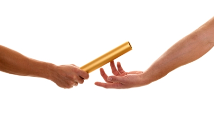 Two people passing a baton
